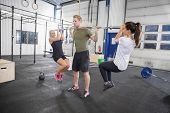 stock photo of squatting  - Squats at the gym with two girls as weights - JPG