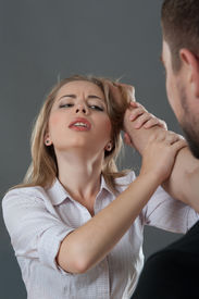 picture of wife-beater  - Young fair-haired woman holding man at his hand looking suppliantly at him while he grasps her hair. Isolated on grey background ** Note: Shallow depth of field - JPG