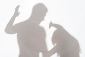 stock photo of wife-beater  - Silhouette of man striking the woman who cannot to protect herself - JPG