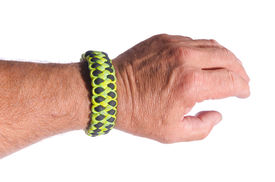 foto of paracord  - Mans arm with a double piranha weave survival bracelet in camouflage paracord - JPG