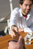 picture of waiter  - Close up portrait of a young man handing a waiter payment card at restaurant - JPG