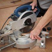 stock photo of laminate  - Worker cut wooden batten for laminate floor floating wood tile - JPG