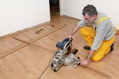 picture of laminate  - Worker cut wooden batten for laminate floor floating wood tile - JPG