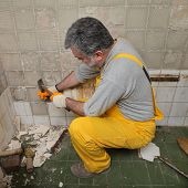 foto of chisel  - Adult worker remove demolish old tiles in a bathroom with hammer and chisel - JPG