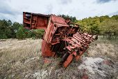 foto of junk-yard  - rusty combine harvester on junk yard near Illinci village in Chernobyl Nuclear Power Plant Zone of Alienation Ukraine - JPG