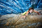 Постер, плакат: Rock climber climbing up a cliff