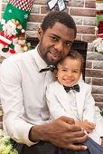 stock photo of new years baby  - Happy black father and baby boy cuddling by fireplace - JPG