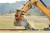 picture of track-hoe  - A large tracked hoe or excavator working at a construction site to extend an airport runway - JPG