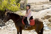 picture of horse girl  - sweet beautiful young girl 7 or 8 years old riding pony horse and smiling happy wearing safety jockey helmet posing outdoors on countryside in summer holiday - JPG