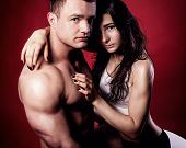 picture of nude couple  - Portrait of handsome athletic couple over red background - JPG