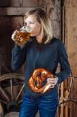 stock photo of pretzels  - Photo of a beautiful blond woman eating and drinking a beer and pretzel inside an old barn - JPG