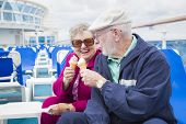 stock photo of passenger ship  - Happy Senior Couple Enjoying Ice Cream On The Deck of a Luxury Passenger Cruise Ship - JPG