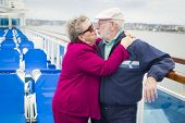stock photo of passenger ship  - Happy Senior Couple Kissing on the Deck of a Luxury Passenger Cruise Ship - JPG