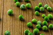 foto of sweet pea  - Organic frozen baby sweet peas on wood board. ** Note: Shallow depth of field - JPG