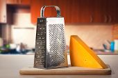 stock photo of shredded cheese  - cheese grater and a big piece of cheese on the kitchen table - JPG