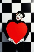 stock photo of mime  - Portrait of a male mime artist holds large red heart expressing love - JPG