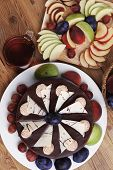 stock photo of hot-chocolate  - whole big chocolate cream brownie cake topped with white chocolate and cream flowers with hot tea cup decorated with fruits apple plum and grape on plate on wooden table - JPG