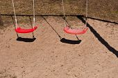 stock photo of swing  - Two empty red swings at childrens playground - JPG