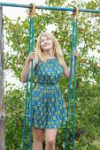 pic of swing  - Blonde student girl iBlonde student girl in feminine silk sundress is standing on handmade swingn feminine silk sundress is standing on handmade swing - JPG