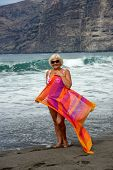 pic of canary  - Full length portrait of elderly woman that is standing on black volcanogenic sand of Guios beach with beach wrap in hands on surf waves and cliff background in Los Gigantes Tenerife Canary Islands - JPG