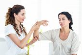 stock photo of hypnotizing  - Therapist holding her patients arm on white background - JPG