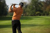 stock photo of swings  - Young man swinging golf club - JPG