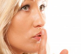 foto of hush  - Woman asking for silence or secrecy with finger on lips hush hand gesture - JPG