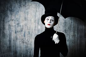 stock photo of pantomime  - Portrait of a male mime artist standing under umbrella expressing sadness and loneliness - JPG