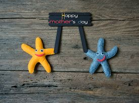 stock photo of i love you mom  - Happy mothers day with i love you mom message idea from colorful fabric starfish on wooden background abstract wooden texture mother - JPG