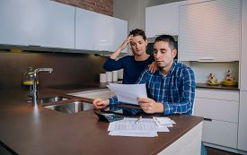 stock photo of unemployed people  - Unemployed young couple with many debts reviewing their bank accounts - JPG