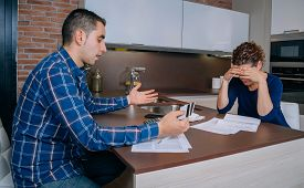 image of conflict couple  - Desperate and unemployed young couple reviewing their credit card debts - JPG