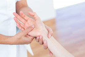stock photo of physiotherapist  - Physiotherapist massaging her patients hand in medical office - JPG