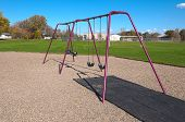 stock photo of swingset  - a four swing swingset at a playground  - JPG