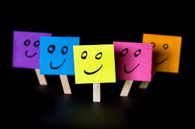 picture of feeling better  - sticky notes with happy faces isolated on a black background for a happy team concept - JPG