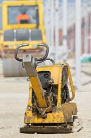 picture of vibration plate  - Vibrating plate compactor standing on gravel ground at construction site - JPG