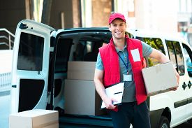 stock photo of packages  - Colorful picture of courier delivers package - JPG