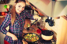 foto of stir fry  - Woman in kitchen cooking stir fry frozen vegetables and tasting - JPG