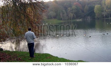 Picture or Photo of Man stands alone beside the lake. evening. autumn. fall. water. man enjoying beautiful landscape scene.