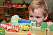 image of nursery school child  - child play with bus train toy in kindergarten - JPG