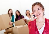 stock photo of moving van  - Group of girls calling the moving van while packing in boxes - JPG