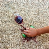 Постер, плакат: glass of red wine fell on carpet wine spilled on carpet Female hand cleans the carpet with a spong