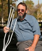 picture of disabled person  - older gentleman resting on a park bench while holding his crutches and contemplating his accident - JPG
