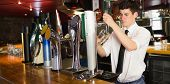 Barkeeper holding glass standing in front of beer dispenser at bar poster