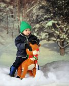 foto of rudolph  - An adorable preschooler in the snow sitting on a large toy Rudolph - JPG