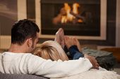 stock photo of cuddling  - Couple sitting on sofa at home in front of fireplace rear view - JPG