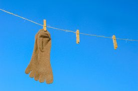 pic of clotheslines  - Odd socks hanging on a clothesline on a sky background - JPG