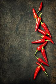 stock photo of red hot chilli peppers  - Vibrant red mexican hot chilli pepper on old background - JPG