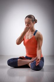 pic of pranayama  - Beautiful sporty fit yogini woman practices pranayama breath control exercise in yoga asana Padmasana  - JPG
