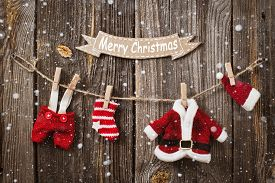 foto of clotheslines  - Santa Claus clothes on a clothesline on a wooden background with Merry Christmas sign - JPG