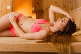 foto of sauna woman  - Portrait of young woman relaxing in wooden finnish sauna - JPG